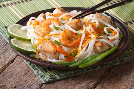 Rice noodles with seafood and chicken, vegetables closeup photo