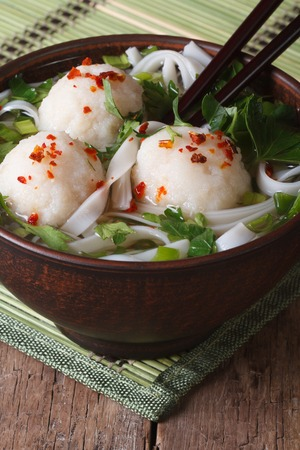 cooked pepper ball: rice noodle soup with fish balls in a bowl and chopsticks close-up. vertical