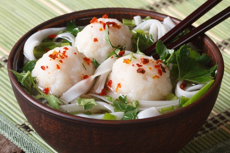 cooked pepper ball: Asian soup with fish balls, fresh herbs and rice noodles in a bowl with chopsticks close-up. horizontal