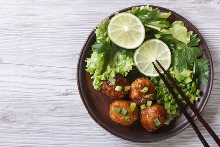 Fish balls in curry sauce on a plate with fresh herbs. top view of a horizontal