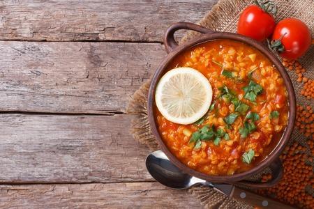 テーブルの上のレモンと野菜のクローズ アップと赤レンズ豆のスープ。上から水平ビュー