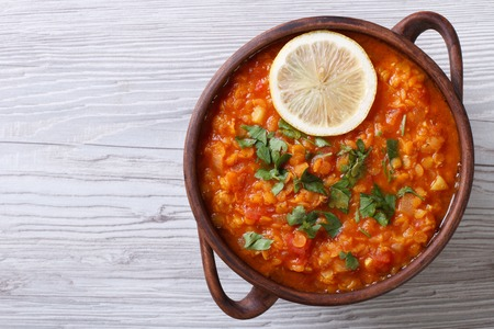 lenteja: sopa de verduras con lentejas rojas y cerca de los tomates en la mesa. vista horizontal desde arriba