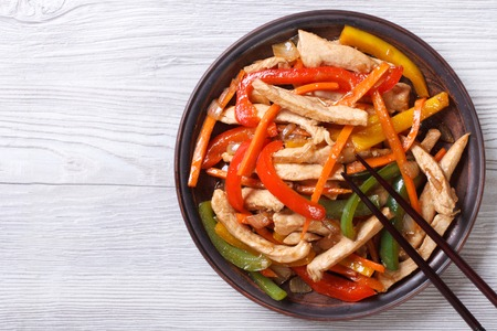 stir fry: Asian food: chicken in sweet and sour sauce with vegetables close-up on a plate. top view of a horizontal