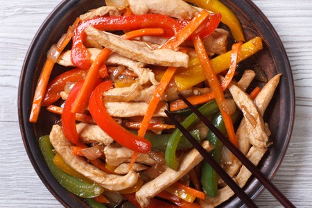 Asian food chicken with vegetables close-up on a plate. top view of a horizontal photo
