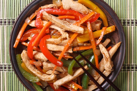 Chinese chicken with vegetables macro on a plate and chopsticks. horizontal view from above photo