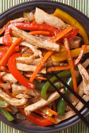 Chinese chicken with vegetables macro on a plate and chopsticks. vertical top view photo