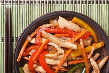 Asian chicken with vegetables macro on a plate and chopsticks. horizontal view from above photo