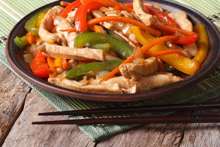 Asian food: chicken with vegetables close-up and chopsticks on the wooden table. horizontal photo