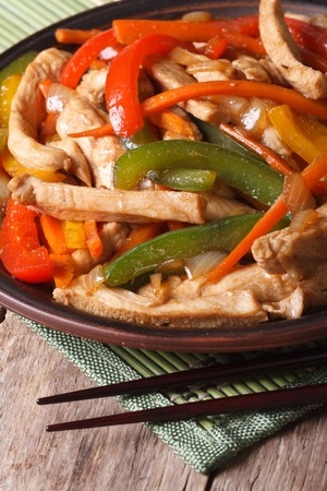 Chinese food: chicken with vegetables closeup and chopsticks on the wooden table. vertical photo