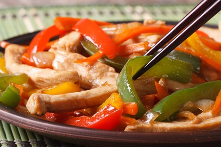 chicken with peppers, carrots macro and chopsticks on the wooden table. horizontal photo