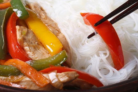 Rice vermicelli with chicken, vegetables and chopsticks. macro horizontal photo