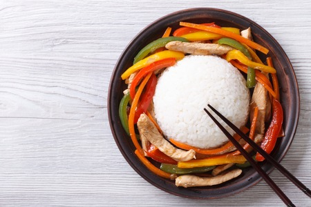 Rice with chicken, vegetables and chopsticks close-up on the table. top view of a horizontal