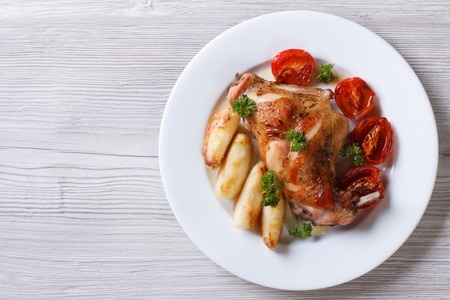 delicious grilled rabbit leg with apples and tomatoes on white plate close-up. horizontal view from above photo