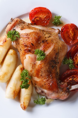 roasted rabbit leg with apples and tomatoes on white plate macro. vertical top view photo