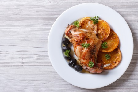 roasted rabbit leg with oranges, olives on a white plate. horizontal view from above photo