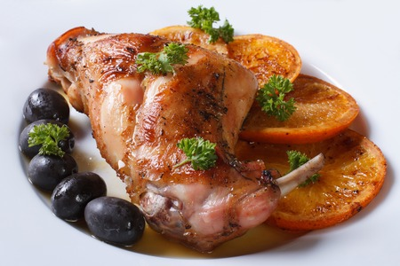 delicious fried rabbit leg with oranges, olives on a white plate close-up. horizontal photo