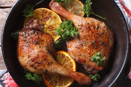roasted duck leg with oranges in a pan close-up. horizontal view from above