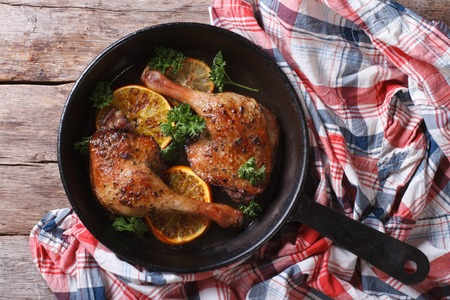 Appetizing roasted duck leg with oranges and parsley in a pan close-up. top view, horizontal, rustic Imagens