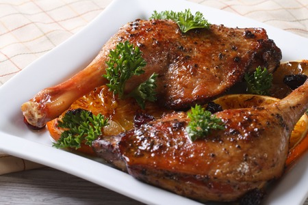 roasted duck leg with oranges on a white plate close up. horizontal