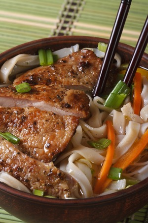 Chinese soup of duck and rice noodle close-up and chopsticks. vertical top view photo
