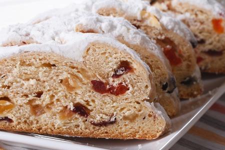 German Christmas fruit bread Stollen sliced macro on a white plate. horizontal photo