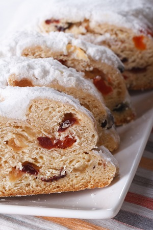 Tasty German Christmas fruit bread Stollen sliced macro on a white plate. vertical photo