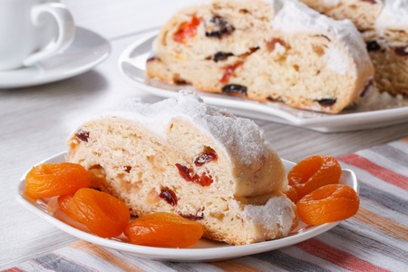 Traditional cake with raisins, dried apricots and candied slices closeup on a white plate. horizontal photo