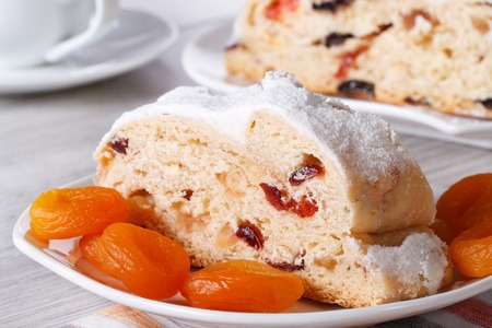 A piece of cake with raisins, dried apricots and candied closeup on a white plate. horizontal photo