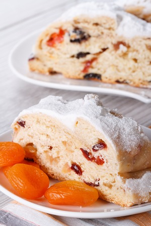 A piece of cake with raisins, dried apricots and candied closeup on a white plate. vertical photo
