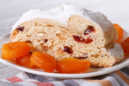 Slice of bread with raisins, dried apricots and candied closeup on a white plate. horizontal photo