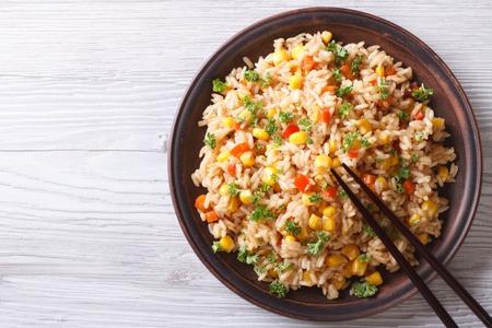 Asian gebratener Reis mit Eiern, Mais und Petersilie close-up auf einem Teller, horizontal von oben