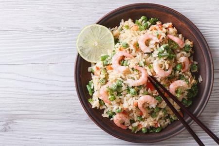 prawn: Arroz japon�s frito con mariscos, huevos y verduras en un plato de cerca, visi�n horizontal desde arriba