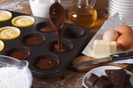 chocolate cake: processes of preparation of chocolate muffins close-up on the table. horizontal Stock Photo