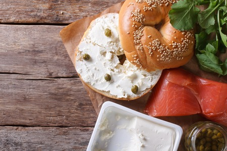 bublik: Fresh bagel with cheese, red fish and ingredients on the table. top view horizontal close-up