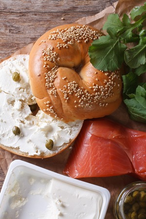 bublik: Bagel and ingredients: fish, cheese, capers on the table close-up. vertical top view