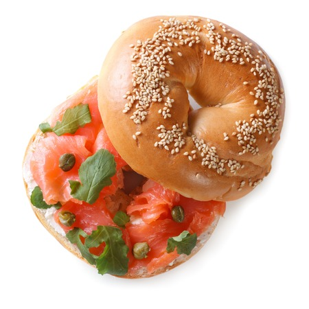 jewish cuisine: delicious bagel with red fish and soft cheese isolated on a white background close-up. top view