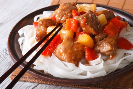 Pork with vegetables and rice noodles close up on a plate. horizontal photo