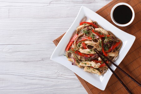 soy sauce: Japanese Yakisoba with chicken and vegetables on a plate
