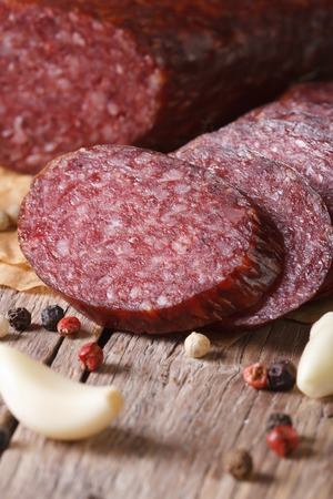 fresh meat: Sliced smoked sausage with spices and garlic on old table. vertical macro Stock Photo