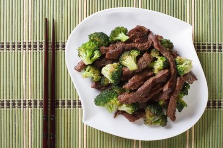 comida japonesa: trozos de carne de res con br�coli en un plato de cerca y palillos. vista horizontal desde arriba Foto de archivo