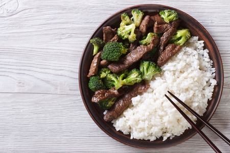 food  restaurant: beef with broccoli and rice on a plate on the table. horizontal view from above