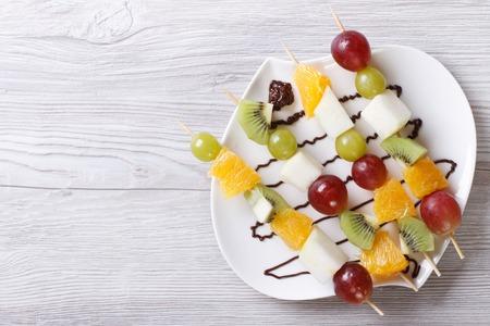 brochetas de frutas: Frutas tropicales en brochetas con salsa de chocolate. vista horizontal desde arriba Foto de archivo