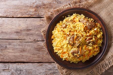 plato de comida: Pilaf asiática deliciosa en una placa de color marrón. visión horizontal de estilo rústico arriba