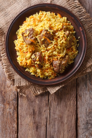 Rice with meat and vegetables on an old table close-up. vertical view above, rustic style