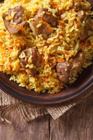 uzbek: Rice with meat and vegetables on an old table macro. vertical view above, rustic style