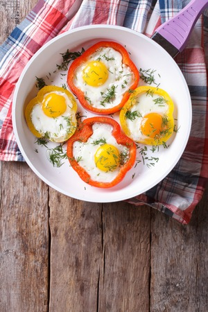 white eggs: fried eggs with yellow and red peppers in a pan. vertical view from above