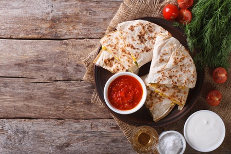 Quesadilla sliced with vegetables and sauces on the table. horizontal view from above