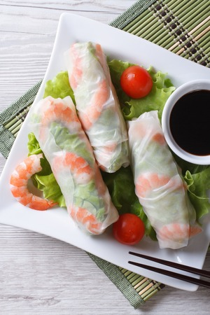 spring roll with shrimp and vegetables on a plate closeup. vertical view from above