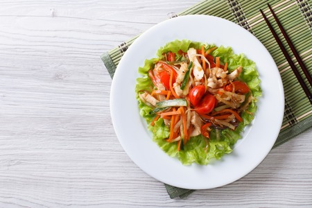 meat dish: Asian warm salad with chicken and vegetables. top view of a horizontal
