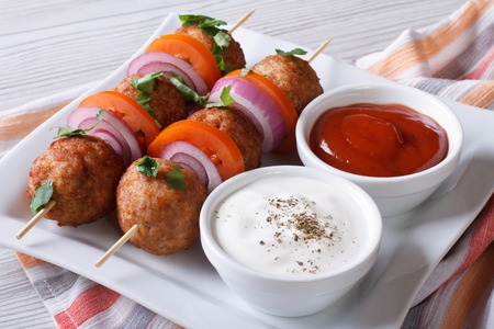 Delicious meatballs on skewers with sauce on a plate close-up. horizontal photo